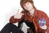 Músico com guitarra vendendo disco compacto