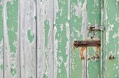 Weathered Wooden Door Peeling Green Paint With Rusty Bolt And Lock