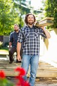 Portrait of mid adult carpenter and coworker carrying wooden planks at construction site