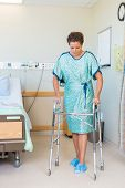 Full length of mid adult female patient walking with the help of walker in hospital