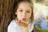 Close-up portrait of a pretty young girl blowing a kiss at the park