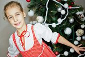 Smiling little girl dressed in white blouse and red pinafore dress with white polka dots stands agai