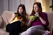 picture of watching movie  - Young girls watching scary movie and eating popcorn - JPG