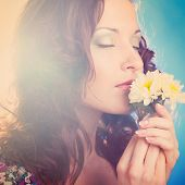 beautiful woman is smelling camomiles on blue background