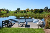 Picnic table by the scenic pond in early autumn time