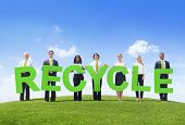 Business People Holding The Word Recycle on a Green Hill