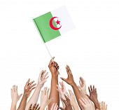 Diverse Multiethnic Hands Holding and Reaching For The Flag of Algeria