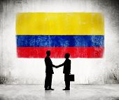Two Businessmen Shaking Hands With Colombian Flag In Background