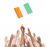 Group Of Multi-Ethnic People Reaching For And Holding The Flag Of Cote D'Ivoire