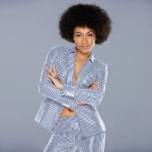 Beautiful glamorous Afro-American woman in a stylish tailored striped slack suit standing looking at