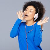 Happy beautiful young African American woman singing along to the music on her headphones as she enj