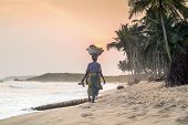 Walking Woman At Beautiful Sunset On A Paradise Beach