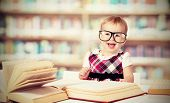 Funny Baby Girl In Glasses Reading A Book In A Library