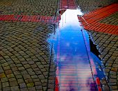 Puddle With The Reflection Of The Sky On The Sidewalk