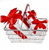 Shopping hand basket full of gift boxes tied with ribbons - isolated on white background