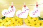 Happy Mothers Day message written on paper hearts with flowers on yellow background