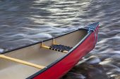 invitation to paddling - red canoe bow with a rope against river flow