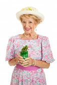 Beautiful senior Southern Belle drinking a traditional mint julep to celebrate Kentucky Derby day.