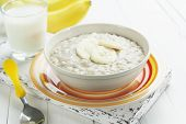 image of porridge  - Porridge with bananas in a yellow bowl and a glass of milk on the table - JPG