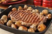 picture of sauteed  - A grilled rib steak and sauteed mushrooms in a cast iron skilled - JPG