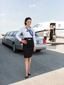 Full length portrait of attractive stewardess standing against limousine and private jet at airport