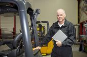 Forklift maintenance engineer holding the manual, ready with his after sales inspection in a worksho