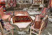 image of goreme  - turkish carpets and leather handbags thrown over wooden furniture on display at a shop in Goreme Turkey - JPG