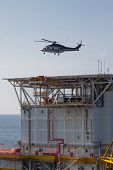 helicopter landing on an offshore oil-plant , service travel to oil and gas platform in offshore.