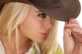 A close up of a cowgirl touching the brim of her hat
