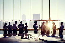 stock photo of reflections  - Group of Business People Discussing at Sunset Reflected Onto Table with Documents - JPG