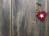 Star heart and antique bronze skeleton key hanging on rustic wood door