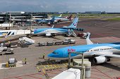 Schiphol Airport With Workers And Departing And Arriving Airplanes