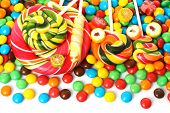 image of lollipop  - Colorful spiral lollipop with chocolate coated candy on white background - JPG