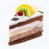 Piece Of Chocolate Cake With Icing And Fresh Fruit Isolated On A White