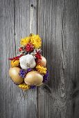 Braided Bunch With Onions, Garlic And Flowers, On Wooden Background