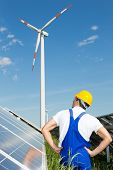 Engineer In Front Of Solar Panels Looks At Wind Turbine