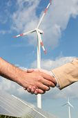 Handshake In Front Of Wind Turbine And Blue Sky