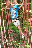 Man Climbs Over Obstacles At High Rope Court