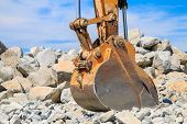 picture of backhoe  - Backhoe bucket with a large pile of rocks in the background against a blue sky - JPG