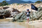 Cute boy dressed as pirate on beach