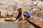 foto of ou  - washing gold in the river woman sieves rock at river Nam Ou in Laos - JPG