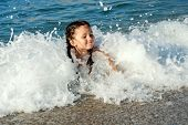 Child Swimming In The Sea In Waves.