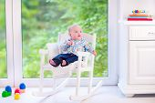 stock photo of daycare  - Cute funny baby adorable little boy wearing a colorful shirt relaxing in a white rocking chair next to a big garden view window at home or daycare center - JPG