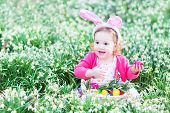 Adorable Toddler Girl Wearing Bunny Ears With Easter Eggs in garden with first spring flowers