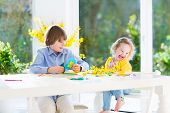Two kids drawing, painting and cutting colorful paper butterflies