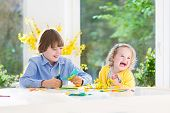 Two Kids painting  in a bright sunny white dining room a big garden view window