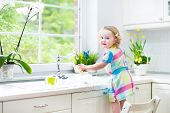 Sweet Curly Toddler Girl washing dishes, cleaning with a sponge and playing with foam in the sink