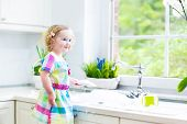 stock photo of window washing  - Cute curly toddler girl in a colorful dress washing dishes - JPG