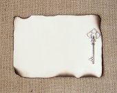 picture of skeleton key  - Burned paper with silver key over burlap - JPG