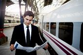Handsome businessman reading newspaper standing in platform of big railway station, successful rich